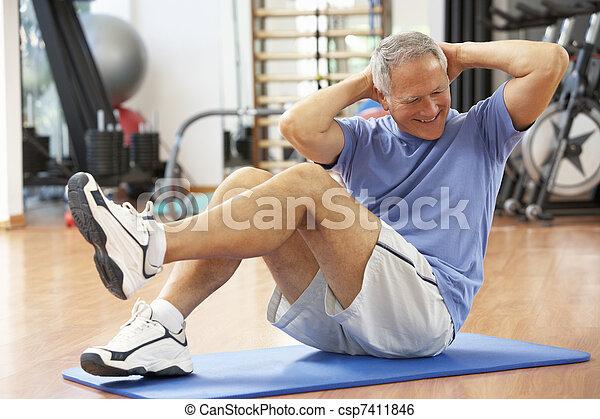 Senior Man Doing Sit Ups In Gym - csp7411846