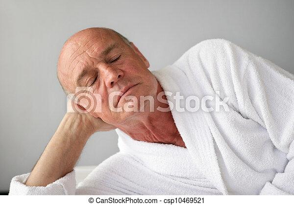 Senior man dozing in a bathrobe - csp10469521