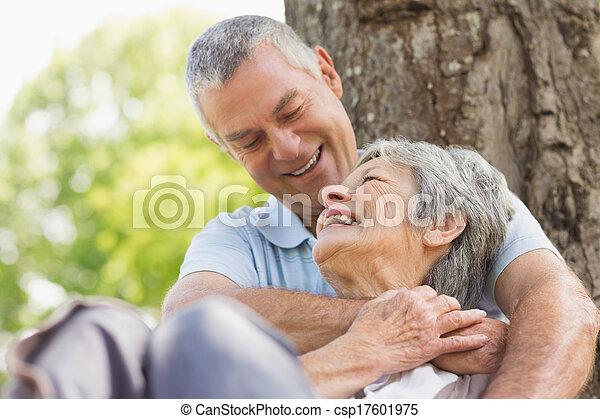Senior man embracing woman from behind at park - csp17601975