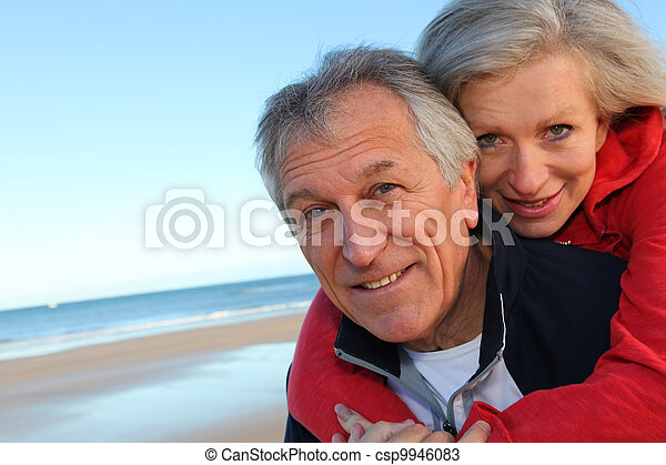 Senior man giving piggyback ride to woman by the sea - csp9946083