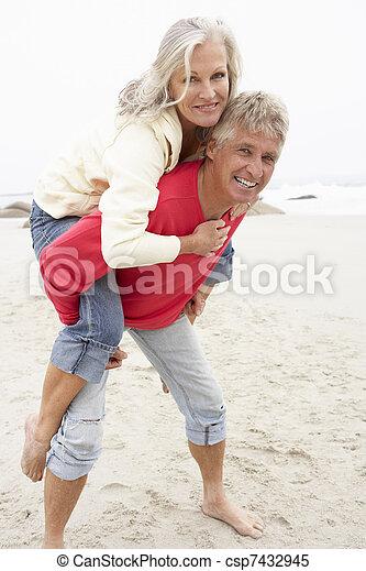 Senior Man Giving Woman Piggyback On Winter Beach - csp7432945