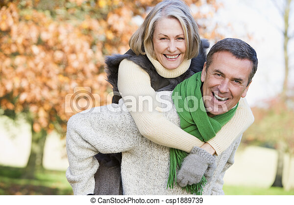 Senior man giving woman piggyback ride - csp1889739