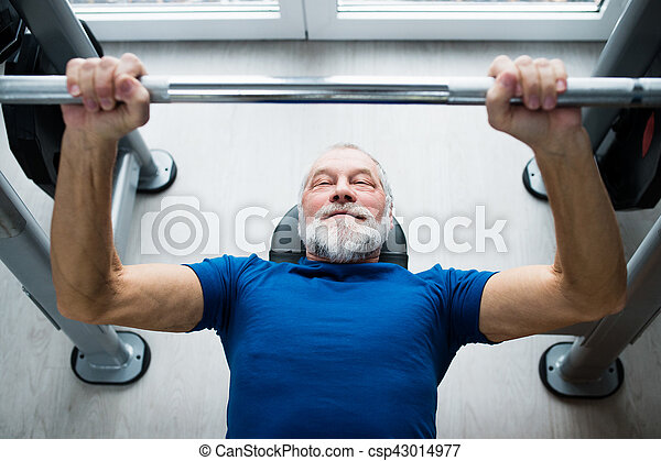 Senior man in gym working out with weights, bench pressing. - csp43014977