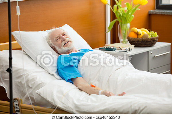 Smiling senior patient with drop counter lying in hospital bed