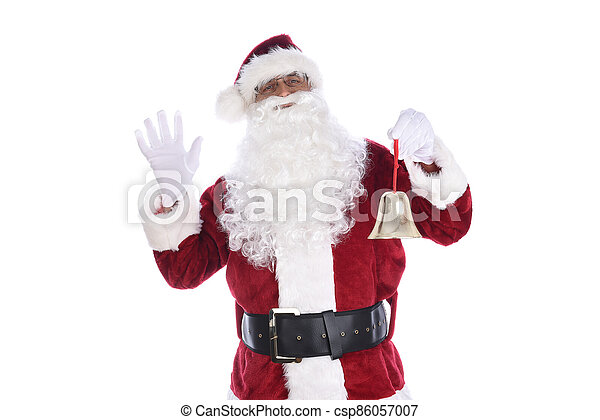 Senior man in traditional Santa Claus costume holding a gold bell ornament in one hand and waving with the other. Isolated on white. - csp86057007