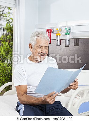 Senior Man Looking At Reports On Bed In Rehab Center - csp37031109