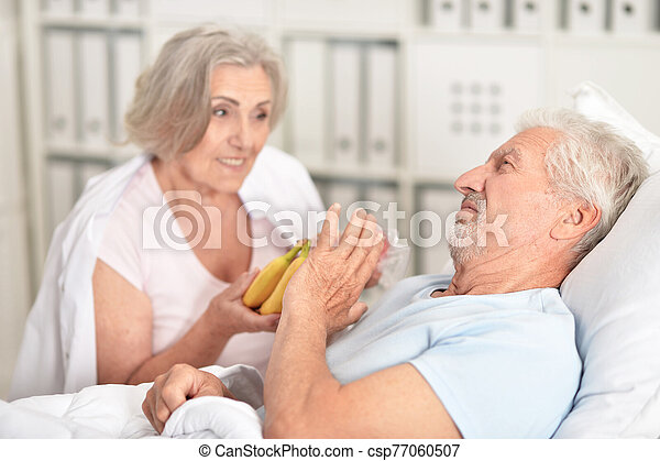 Senior man portrait in hospital with caring wife bringing bananas - csp77060507