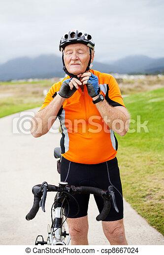 senior man putting his cycling helmet - csp8667024