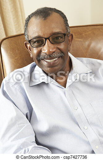 Senior Man Relaxing In Chair At Home - csp7427736