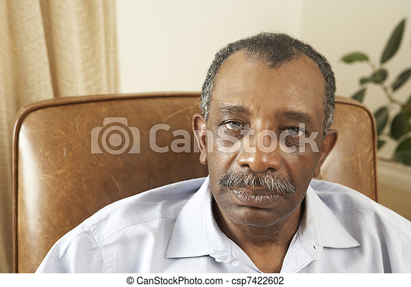 Senior Man Relaxing In Chair At Home - csp7422602