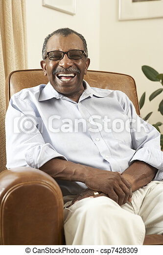 Senior Man Relaxing In Chair At Home - csp7428309