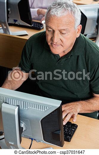 Senior Man Using Computer In Classroom - csp37031647