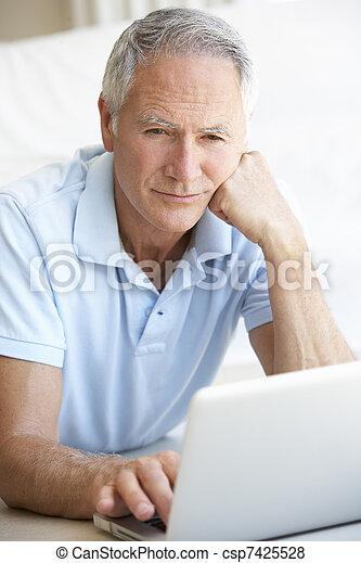 Senior man using laptop computer - csp7425528