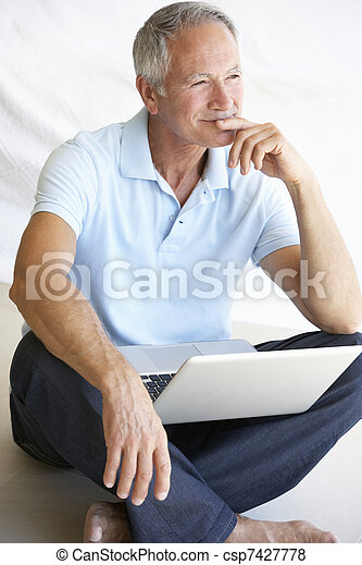 Senior man using laptop computer - csp7427778