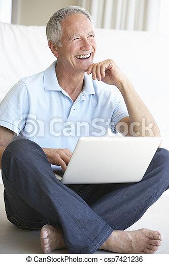 Senior man using laptop computer - csp7421236