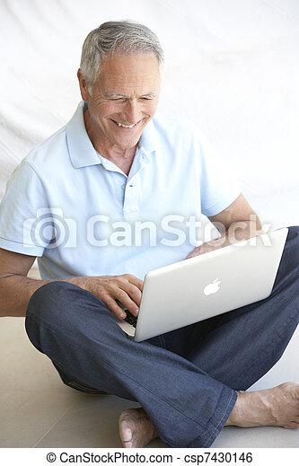 Senior man using laptop computer - csp7430146