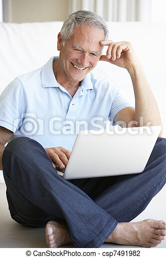 Senior man using laptop computer - csp7491982