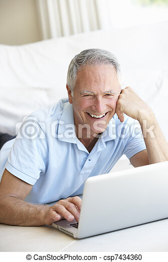 Senior man using laptop computer - csp7434360