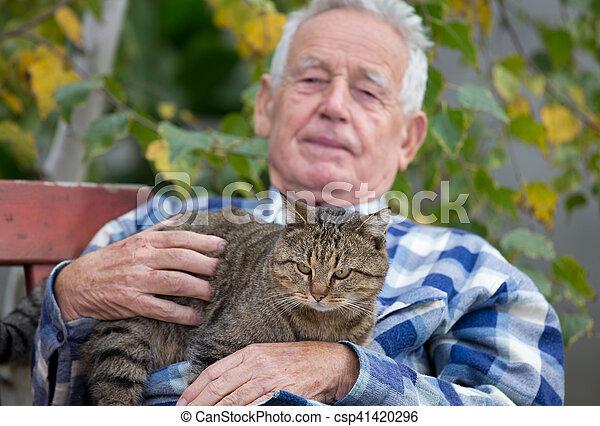 Senior man with cat in courtyard - csp41420296