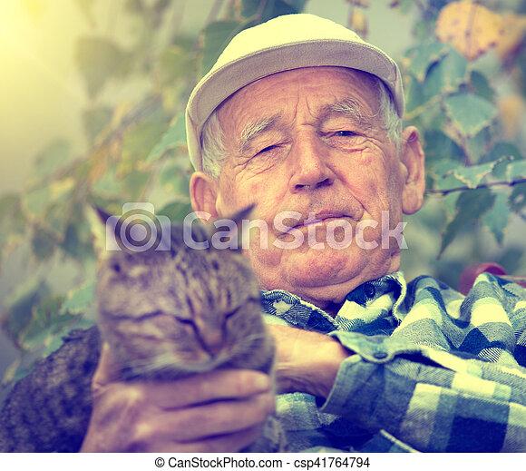 Senior man with cat in courtyard - csp41764794