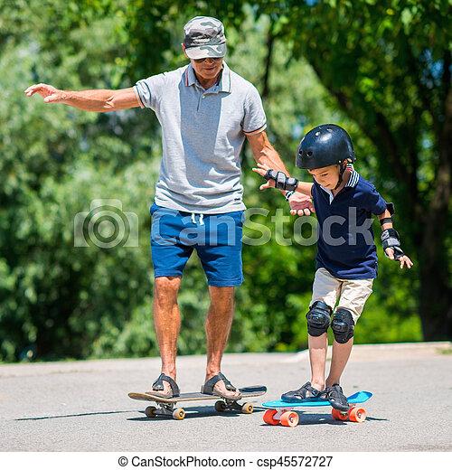 Senior man with little boy skateboarding in park - csp45572727
