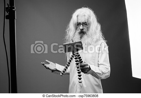 Senior man with long hair and beard vlogging with phone in black and white - csp75963808