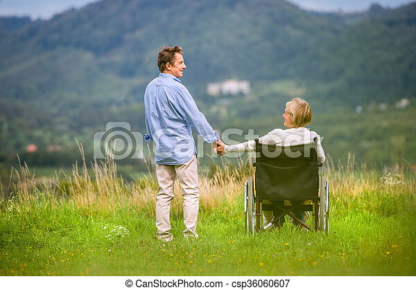 Senior man with woman in wheelchair, green autumn nature - csp36060607