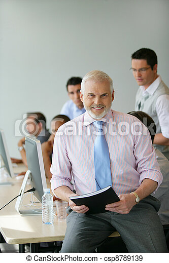Senior manager sitting on a desk in front of his team - csp8789139