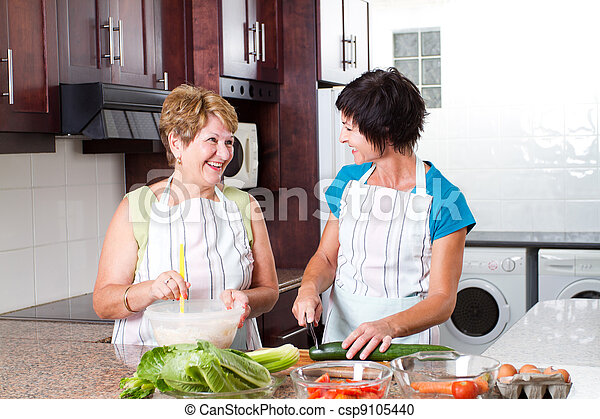 senior mother and middle aged daughter cooking - csp9105440