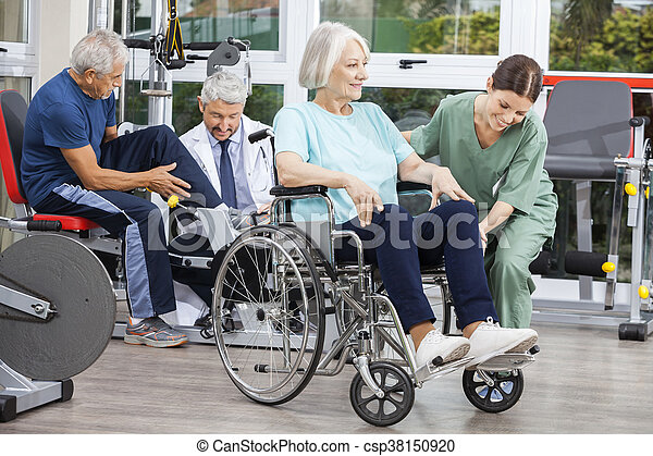 Senior People Being Assisted By Physiotherapists In Rehab Center - csp38150920