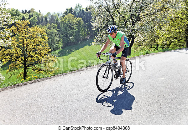 senior riding a bicycle on a road bike - csp8404308