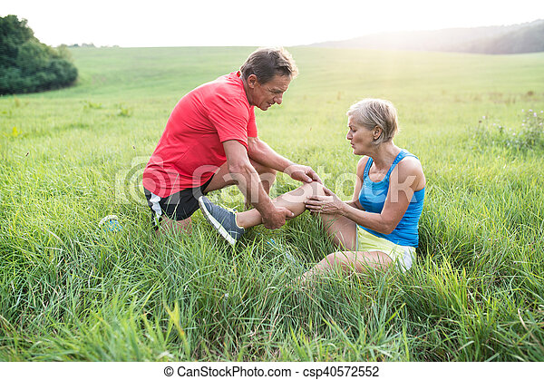 Senior runners in green field. Woman with injured knee. - csp40572552