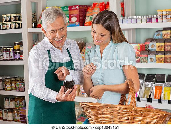 Senior Salesman Assisting Female Customer In Shopping Groceries - csp18043151