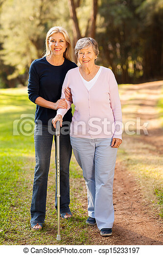 senior woman and caring daughter walking in forest - csp15233197