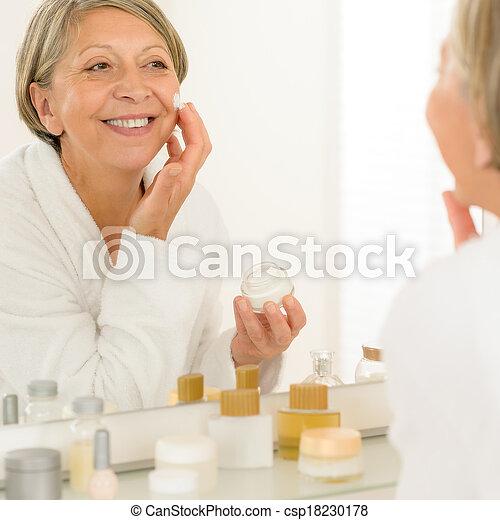 Smiling senior woman apply anti-wrinkles cream looking in bathroom mirror