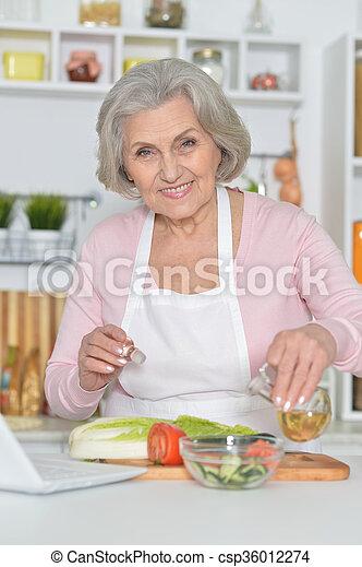 Senior woman cooking in kitchen - csp36012274
