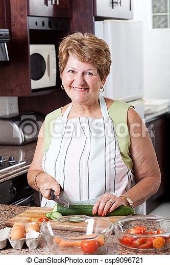 senior woman cooking in kitchen - csp9096721