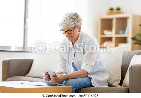 senior woman counting money at home - csp59114278