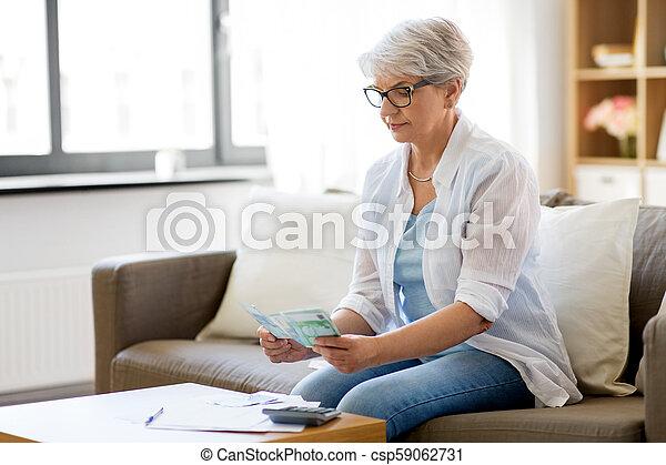 senior woman counting money at home - csp59062731
