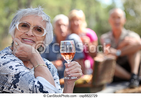 Senior woman enjoying a glass of rose wine with friends on a picnic - csp8822729