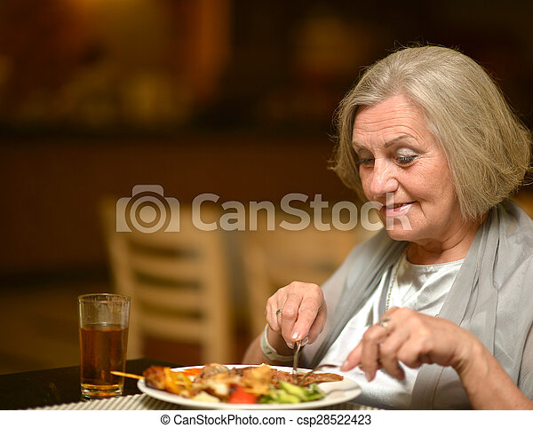 Senior woman having dinne - csp28522423