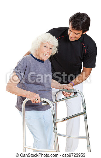 Senior Woman Holding Walker While Trainer Assisting Her - csp9723953