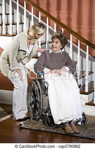 Senior woman in wheelchair with nurse helping - csp3790962