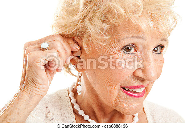 Senior Woman Inserts Hearing Aid - csp6888136