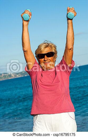 Senior woman lifting weights outdoors. - csp16795175