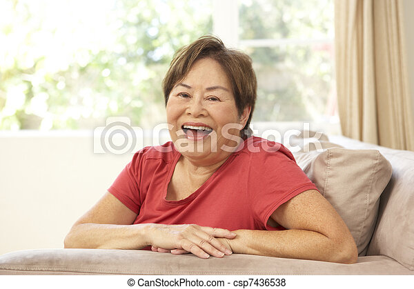 Senior Woman Relaxing In Chair At Home - csp7436538