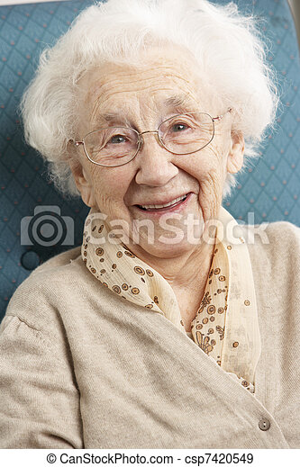 Senior Woman Relaxing In Chair At Home - csp7420549