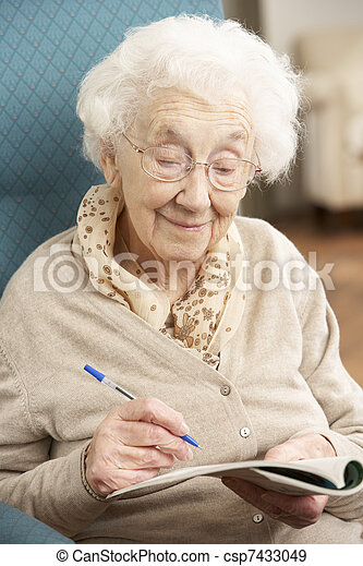 Senior Woman Relaxing In Chair At Home Completing Crossword - csp7433049