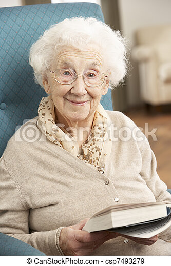 Senior Woman Relaxing In Chair At Home Reading Book - csp7493279