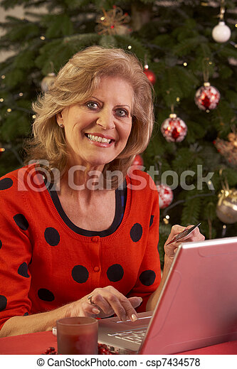 Senior Woman Shopping Online For Christmas Gifts - csp7434578